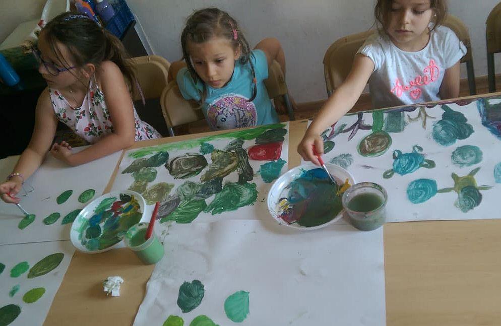 Dzieci przy stole malują obrazki farbami