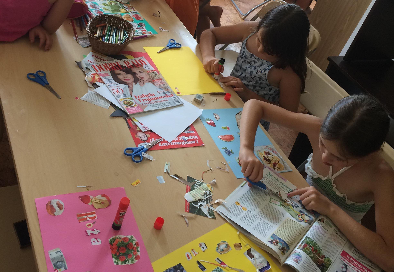 Dwie dziewczynki przy stole tworzą kolaże z wycinków z gazet