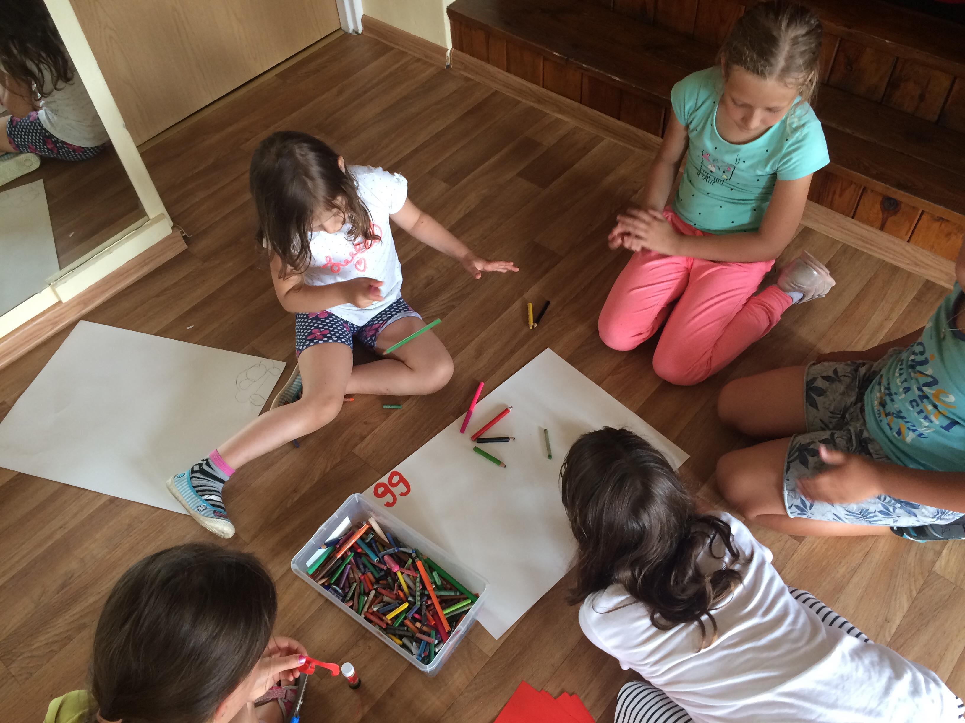 Dzieci siedzą na podłodze i przygotowują rysunek