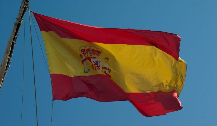 Flaga Hiszpanii. Czerwony pasek na górze, w środku żółty, pod nim znów czerwony. Na środku godło