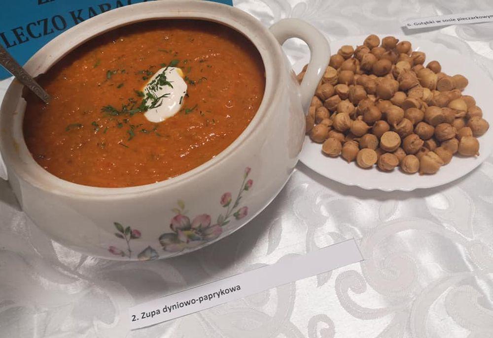 Waza z zupą dyniowo-paprykową. Obok talerz z groszkiem ptysiowym
