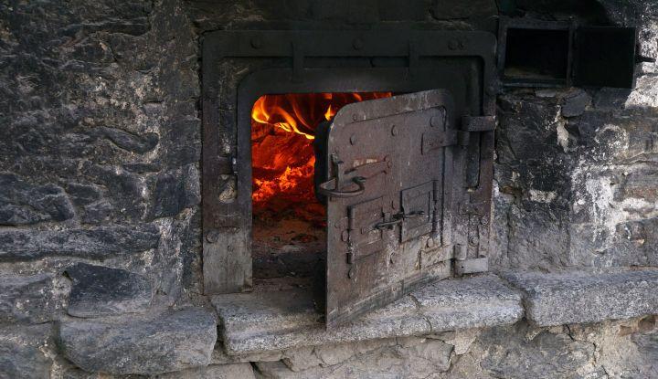 Piec z otwartym paleniskiem. Przez uchylone drzwiczki widać ogień