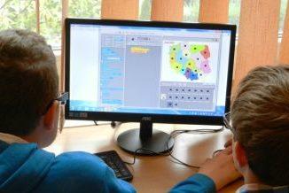 Dwoje dzieci siedzące tyłem. Przed nimi komputer na którym widać mapę Polski