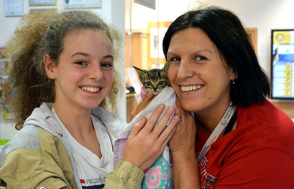 Kobieta w czerwonej bluzce i młoda dziewczyna z kręconymi włosami. Kobieta trzyma w rękach małe kotka
