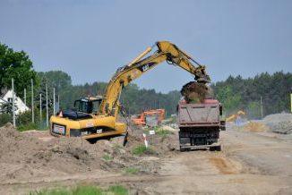 Budowa trasy S17. Żółta koparka przerzuca ziemię na ciężarówkę