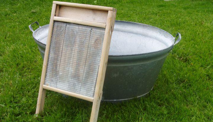 Stara drewniano-metalowa tara do prania oparta o balię do prania