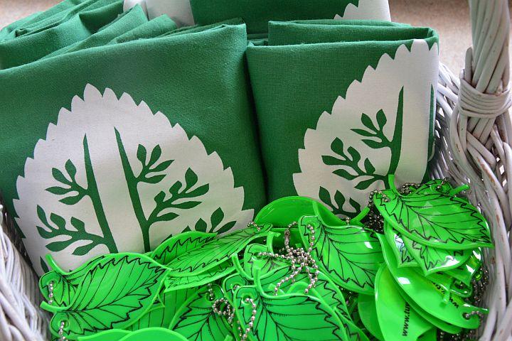 Zielone odblaski w kształcie liścia wiązu i zielone płócienne torby na zakupy