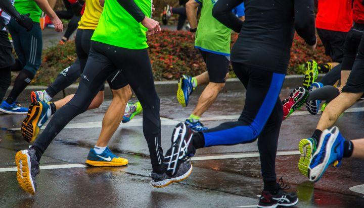 Maratończycy biegną po mokrym asfalcie