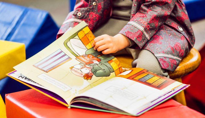 Książka, któej kartki przekłada dziecko. widać tylko dłonie i część tułowia