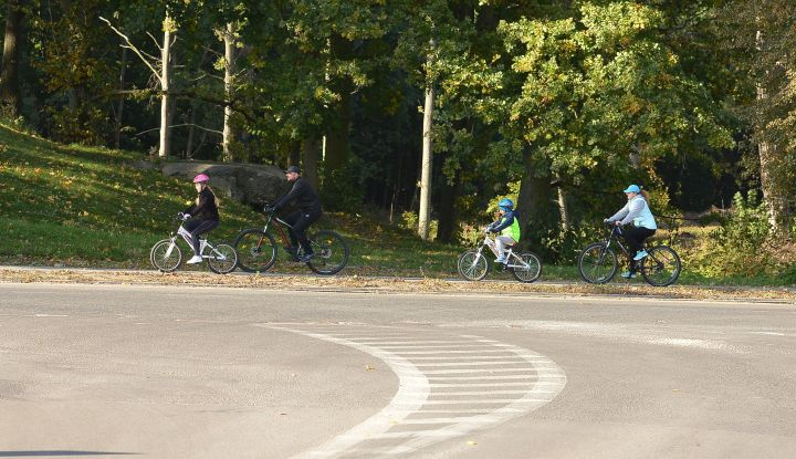 Rodzina na rowerach jadąca po ścieżce rowerowej w gminie Wiązowna