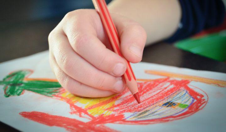 Dziecięca dłoń z czerwoną kredką rysująca kolorowy obrazek