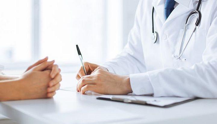 Dłonie lekarza wypisującego zalecenia