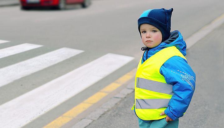 Dziecko w kamizelce odblaskowej stoi przy przejściu dla pieszych