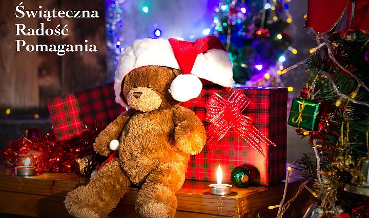 Miś w czapce Mikołaja siedzi oparty o prezent zapakowany w papier w szkocką kratę