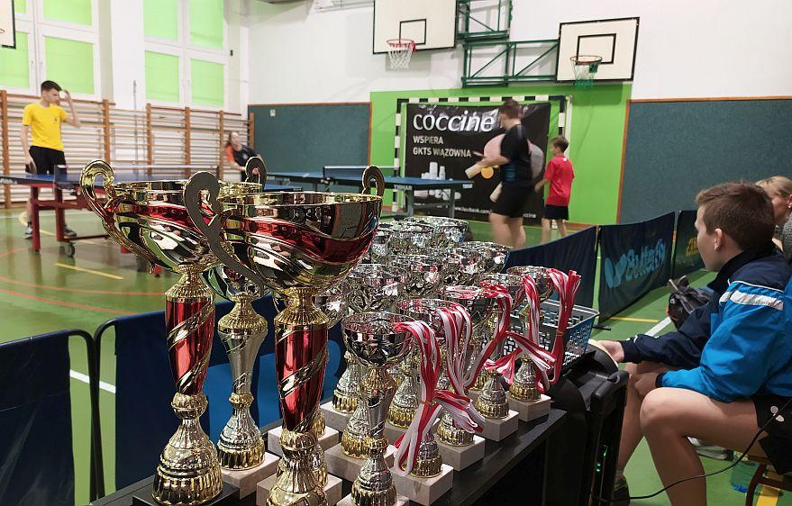 Turniej tenisa stołowego w hali szkoły w Wiązownie. Puchary na pierwszym planie