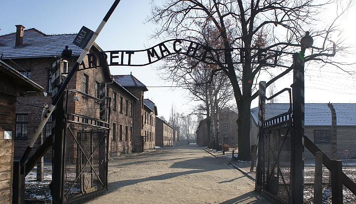 Brama obozu koncentracyjnego Auschwitz-Birkenau. W tle budynki obozu