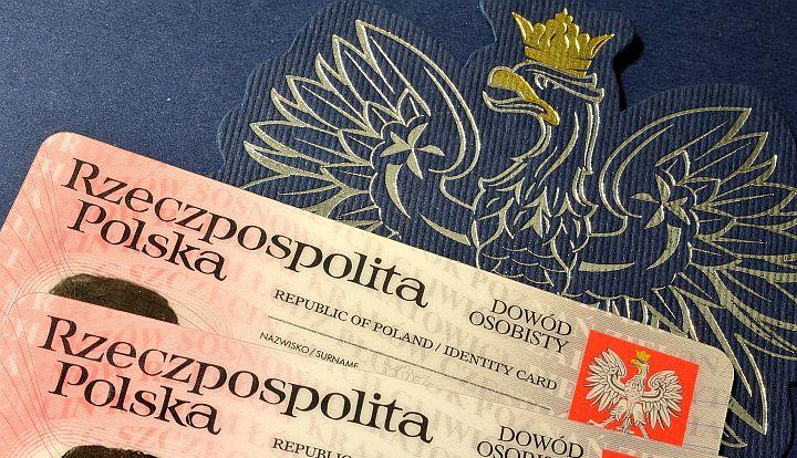 Polski dowód osobisty leży na niebieskim tle z godłem Polski - orłem w złotej koronie