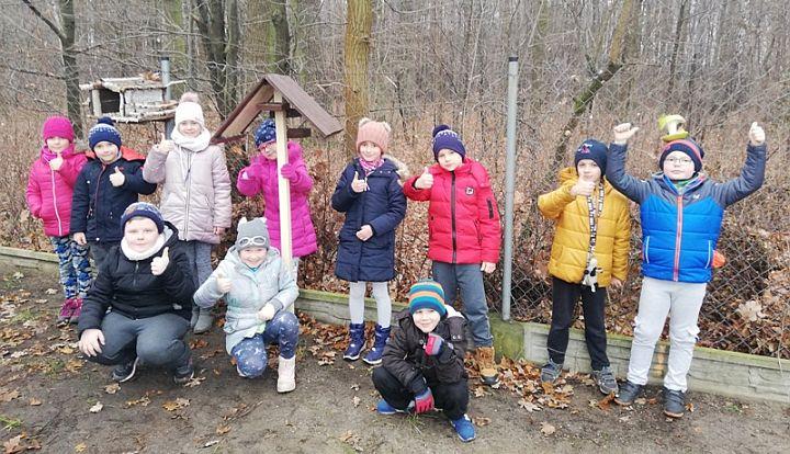 Dzieci ze szkoły w Zakręcie pozują przy zainstalowanych przez siebie karmnikach dla ptaków