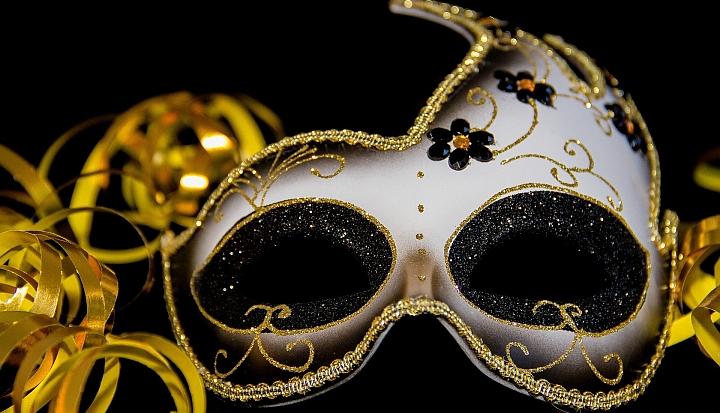 Karnawałowa maska na czarnym tle. Obok złote serpentyny