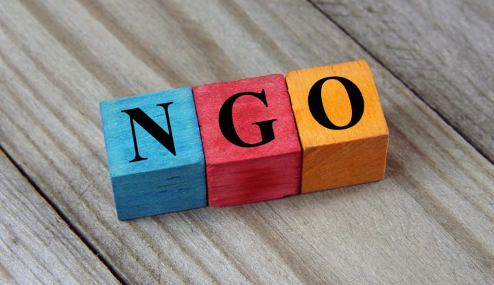 Napis NGO ułożonych z klocków - niebieskiego, czerwonego i żółtego