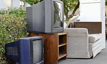 Odpady wielkogabarytowe. Dwa duże i stare telewizory, stara szara kanapa i biała lodówka stoją przed dodmem