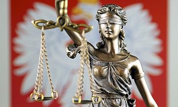 Temida - symbol prawa. Figurka kobiety z zasłoniętymi oczami, w ręku trzyma wagę. W tle godło Polski