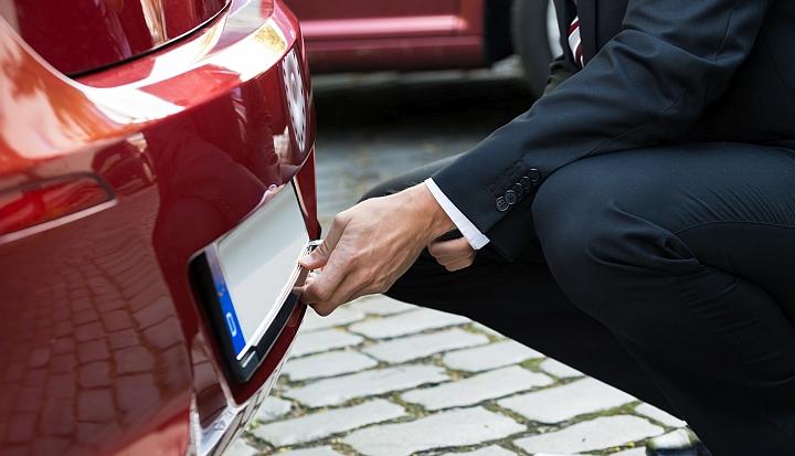 Mężcztzna w czarnym garniturze klęczy z tyłu czerwonego pojazdu i zmienia tablicę rejestracyjną