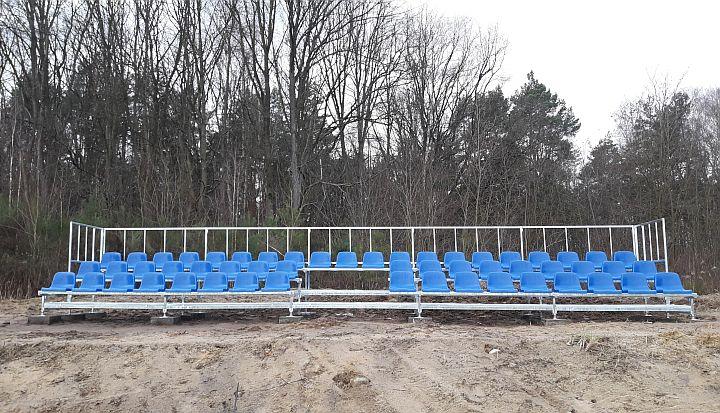 Nowa trzyrzędowa trybuna sportowa na boisku KS Glinianka z niebieskimi siedziskami