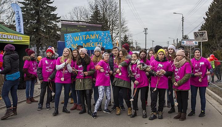 Grupa wolontariuszy w różowych koszulkach witająca zawodników na mecie Półmaratonu Wiązowskiego