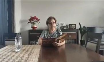 Starsza kobieta z książką w ręku siedzi przy stole i czyta bajkę dla dzieci