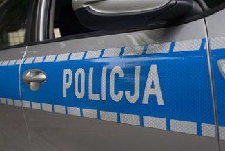 Fragment samochodu policyjnego. biały napis policja na niebieskim pasie