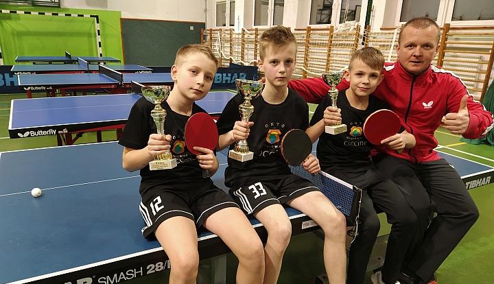 Zwycięzcy Szkolnej Ligi Tenisa Stołowego z pucharami i trenerem