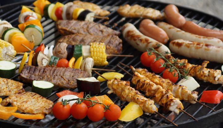 Grill, a na nim szałyki, kiełbaski, mięso, warzywa - pomidory, papryka, kukurydza