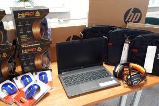 Na stole leży sprzęt komputerowy. Od lewej myszki, słuchawki, na środku laptop, po prawej torby