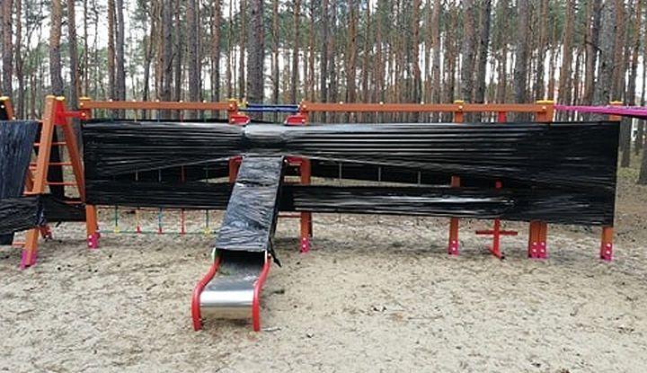 Urządzenie na placu zabaw zabezpieczone czarną folią