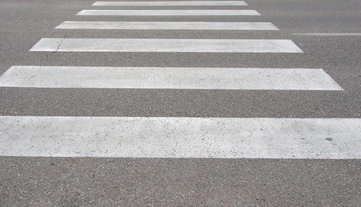 Przejście dla pieszych. Białe pasy na asfaltowej drodze