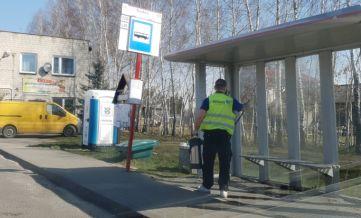 Przystanek autobusowy. Mężczyzna w odblaskowej kamizelce dezynfekuję wiatę przystankową od środka