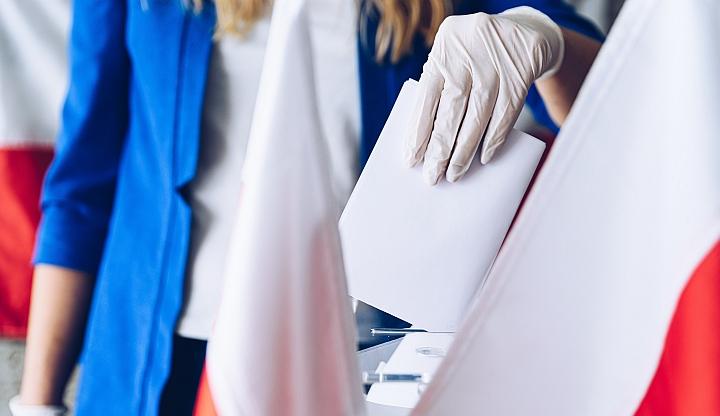Na pierwszym planie ręka kobieca w jednorazowej rękawiczce wrzucająca kartę do urny. W tle kobieta od pasa w górę w białej koszulce i błękitnej marynarce stoi na tle biało-czerwonej flagii