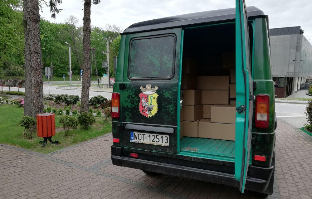 Zielony samochód zaparkowany przed Urzędem Gminy Wiązowna. W nim pudełka z przyłbicami ochronnymi