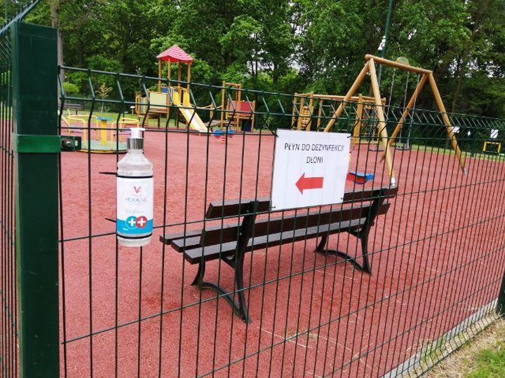 Gminny Park Centrum. Dozownik na płn na ogrodzeniu z lewej. W tle plac zabaw i ławka