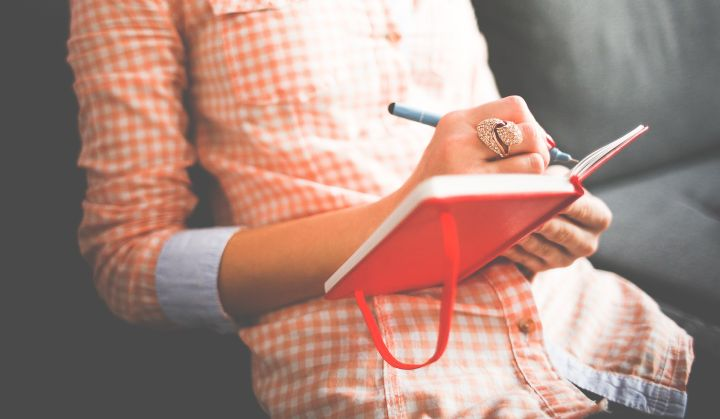 Kobieta w biało-czerwonej koszuli w kartkę siedzi na kanapie i pisze coś w czerwonym notatniku