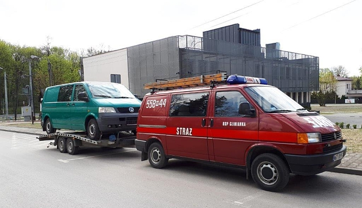 Czerwony samochód straży granicznej, a za nim na lawecie zielone auto