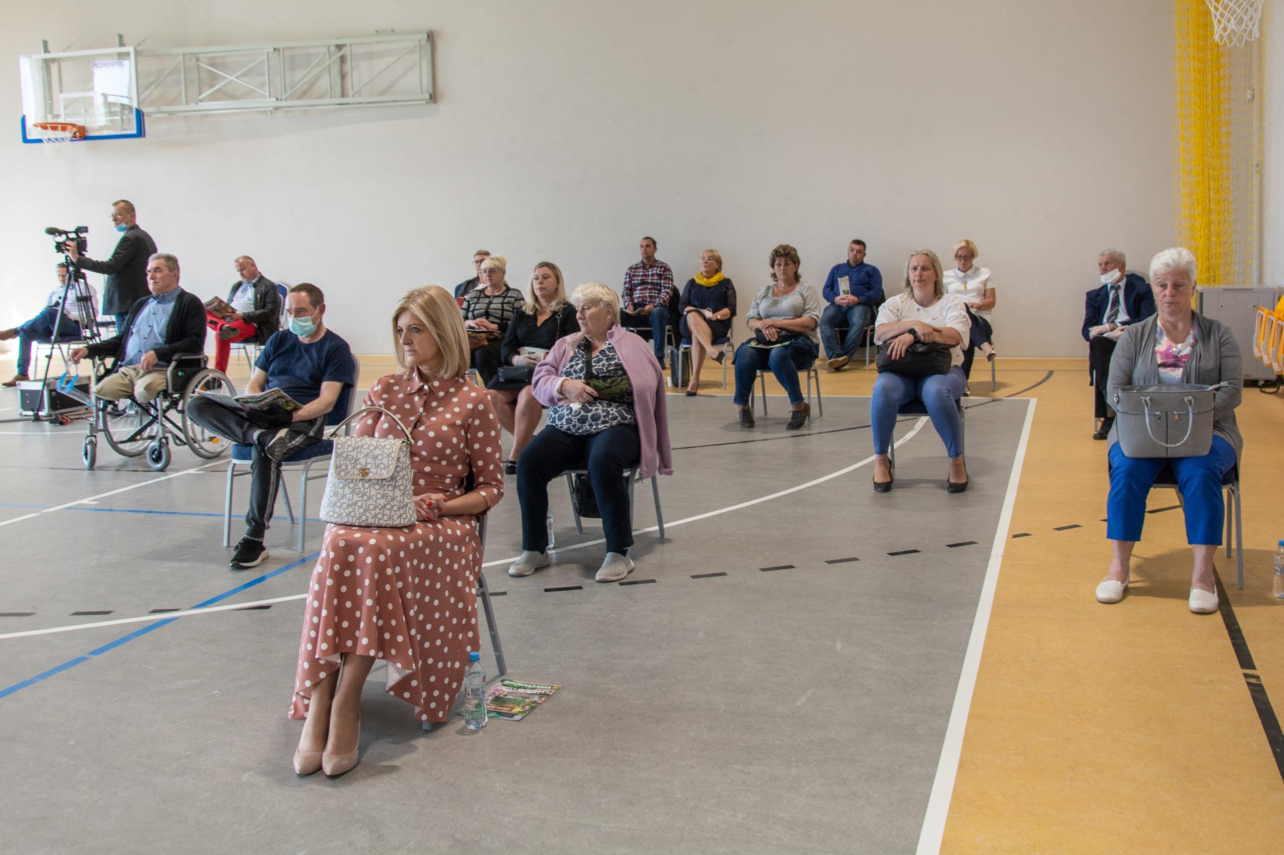 Uroczysta sesja Rady Gminy Wiązowna na sali gimnastycznej w szkole w Gliniance. Sołtysi i zaproszeni goście. Na pierwszym planie radna powiatowa Grażyna Kilbach w sukience w kropki