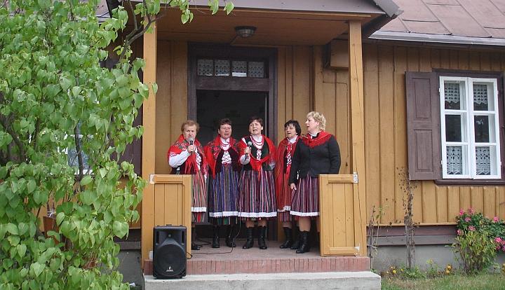 Ganek Izby Regionalnej w Gliniance. Pięć kobiet w strojach ludowych śpiewa piosenkę regionalną