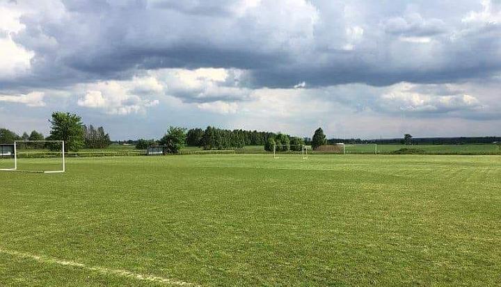 Boisko do piłki nożnej w Rzakcie. Zielona, przystrzyżona trwa. PO lewej stornie bramka. w Tle zachmurzone niebo