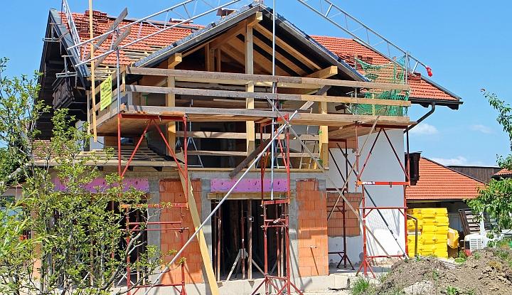 Dom z czerwonej cegły w budowie. Dookoła rusztowanie