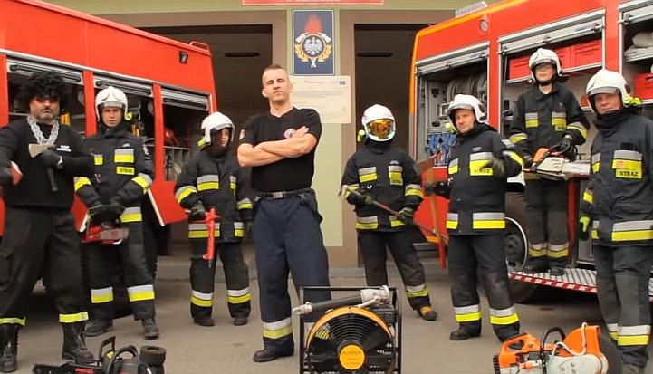 Strażacy z OSP Glinianka w strojach ratowniczych. W tle dwa czerwone wozy strażackie