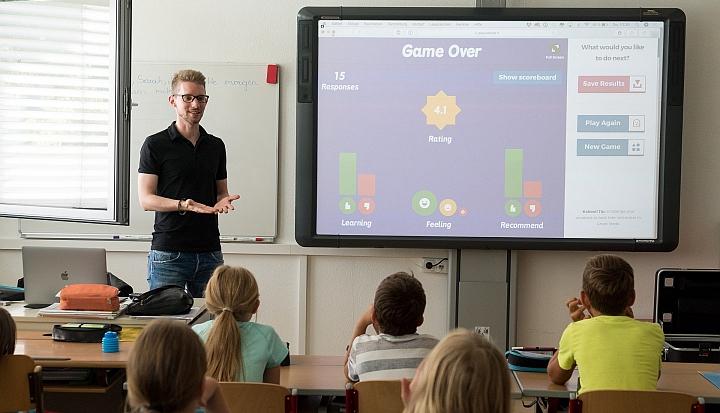 Nauczyciel w czarnej koszulce stoi przodem do uczniów i tłumaczy lekcję, której treść wyświetla się na dużym ekranie