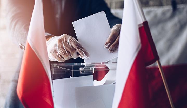 Mężczyzna w jednorazowych rękawiczkach wrzuca kartę do głosowania do urny. Po bokach widać dwie biał0-czerwone flagi