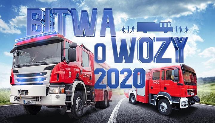 Dwa czerwone wozy strażackie. Na nich napis Bitwa o wozy 2020. W tle niebieskie niebo